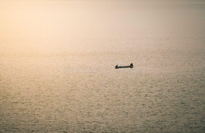 Ett litet fartyg som sv?var i en sj? med staden i morgondimman royaltyfri bild