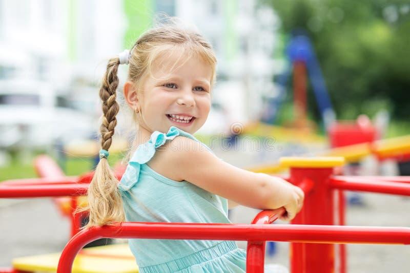 Ett litet gladlynt barn går på lekplatsen Begreppet av barndom, livsstil, uppfostran, dagis arkivbilder