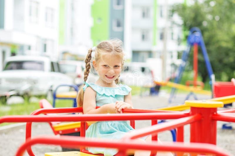 Ett litet gladlynt barn rider en karusell Begreppet av barndom, livsstil, uppfostran, dagis arkivbild