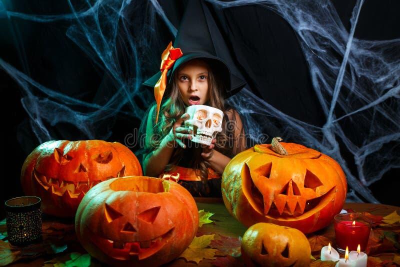 Ett litet häxbarn med halloween söt och godis som ler över spindelnätet och med böjd pumpor som bakgrund arkivfoton