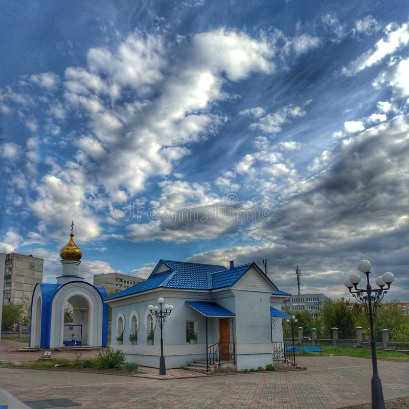 Ett litet hus med ett bl?tt tak, en byggnad med ett Golden Dome och en ljus bl? himmel med vita moln, Sosnovoborsk, Krasnoyarsk r arkivfoton
