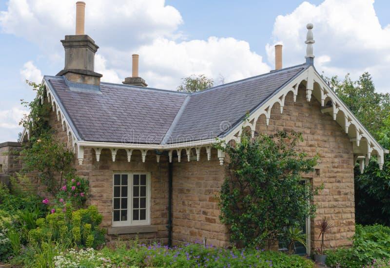 Ett litet idylic hus sitter inom Sheffield Botanical Gardens som tas på en ljus solig dag i sommar arkivfoto