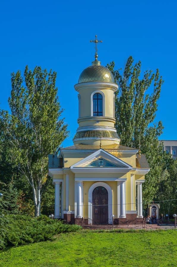 Ett litet kristet kapell bland gröna popplar mot en blå himmel En grön gräsmatta som är främst av den solig dag royaltyfri bild