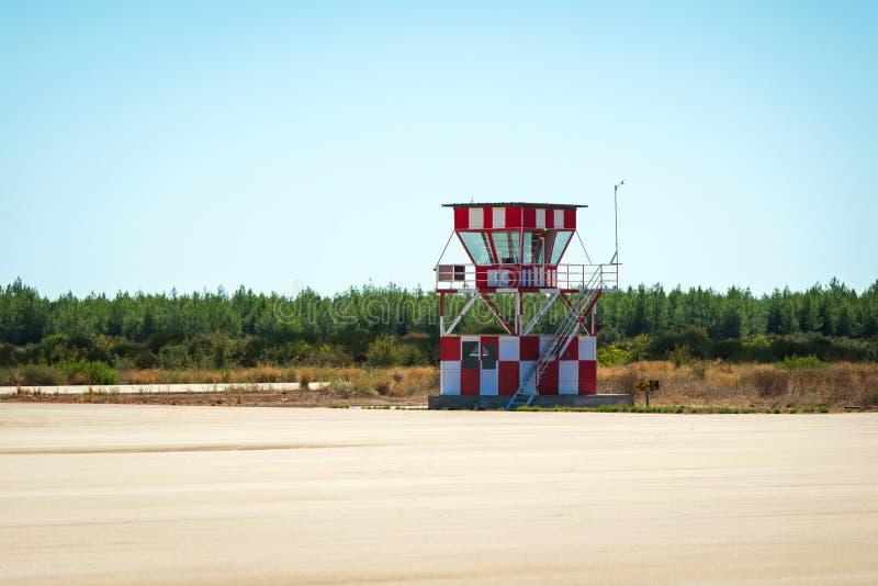 Ett litet rött och vitt flygtrafikkontrolltorn bredvid den tomma flygplatslandningsbanan Gräsplanfält och blå himmel i bakgrunden royaltyfri fotografi