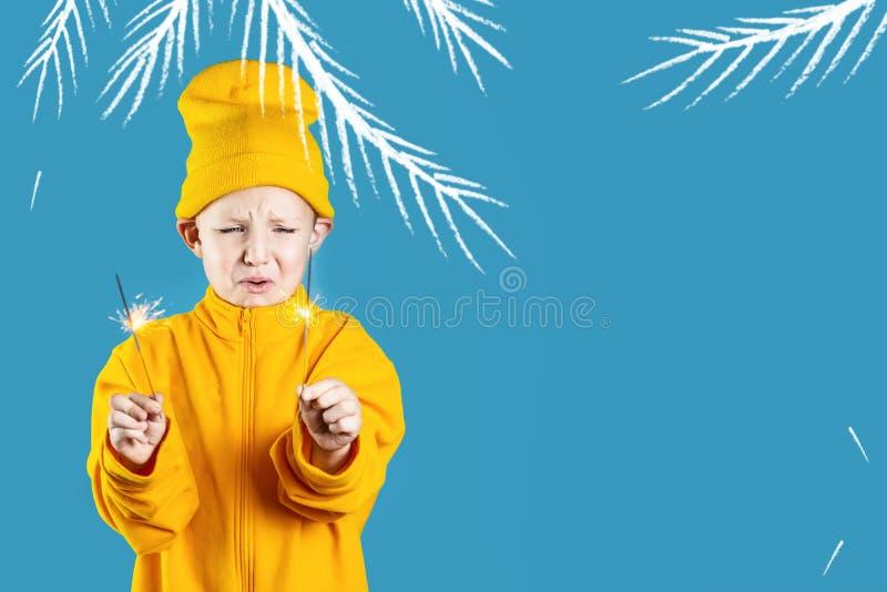 Ett litet, skrämt barn i gul hatt och jacka håller i händerna på sparkler på en blå bakgrund arkivfoton