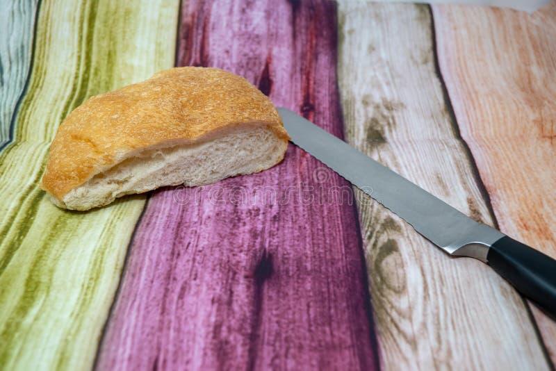 Ett litet släntrar av bröd med en brödklippkniv på en färgrik träbakgrund fotografering för bildbyråer