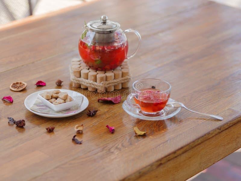Ett ljust bärte i en glass tekanna bredvid ett genomskinligt exponeringsglas, en rund vit platta och torkade frukter på ett trä arkivfoton