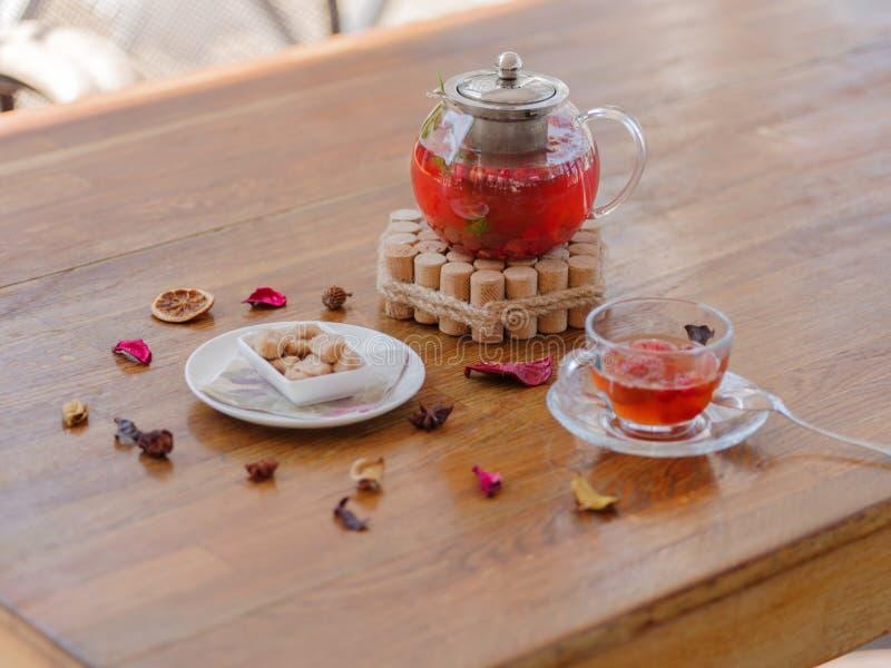 Ett ljust bärte i en glass tekanna bredvid ett genomskinligt exponeringsglas, en rund vit platta och torkade frukter på ett trä fotografering för bildbyråer
