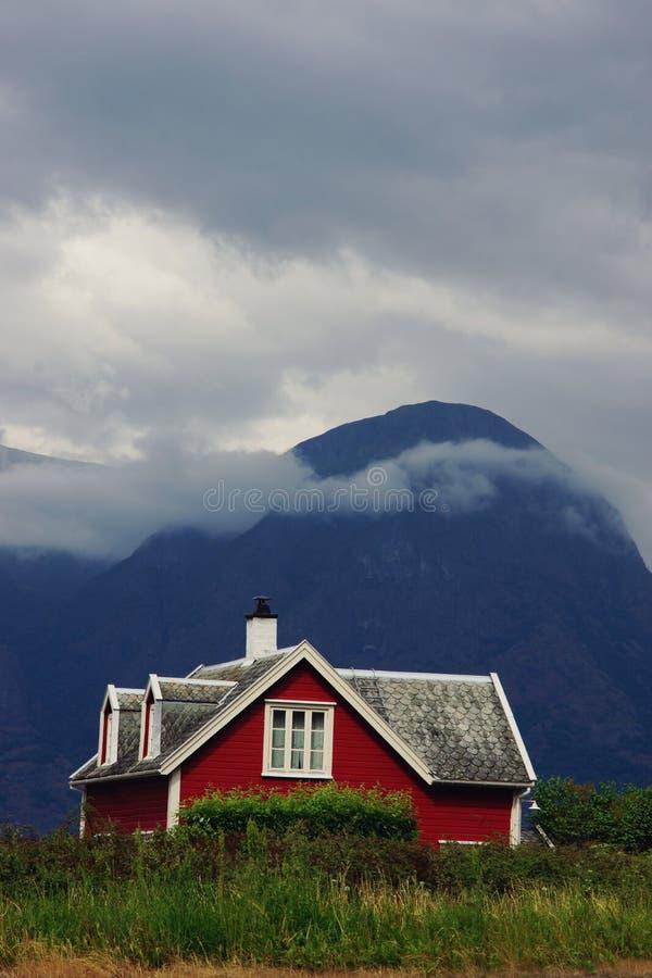 Ett ljust rött hus står bak ett grönt staket mot bakgrunden av ett formidabelt berg i Norge royaltyfri bild