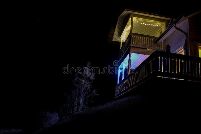 Ett ljust tänt hus på en kulle arkivbild