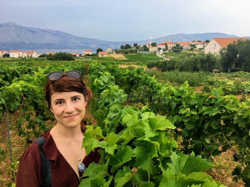 Ett lyckligt anseende för ung kvinna bland breda ut sigvinvingården som växer de lokala grkdruvorna med lilla staden av Lumbarda arkivfoto