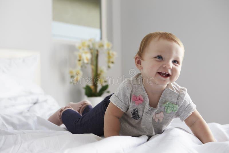 Ett lyckligt behandla som ett barn flickakrypningen på en säng, kopieringsutrymme på vänstersida royaltyfri bild