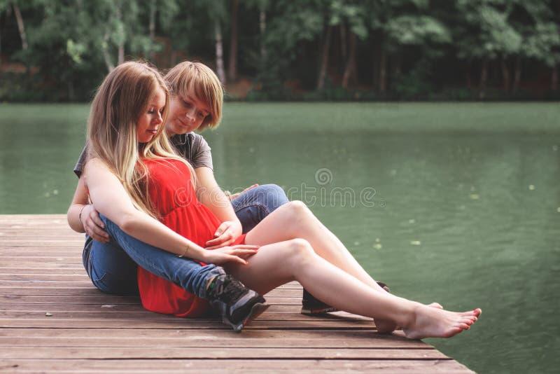 Ett lyckligt gift par Husband hugger en vacker vuxen gravid fru går i en park vid sjön Håll händerna på magen royaltyfri foto