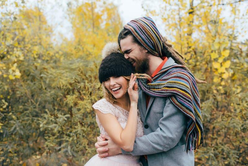 Ett lyckligt par går galet in Bruden i en stucken hatt med en pompon och brudgummen i färgrik halsduk har gyckel bröllop arkivfoton