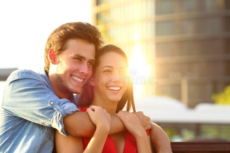 Ett lyckligt par kramar och funderar på solnedgång på en bänk arkivbild