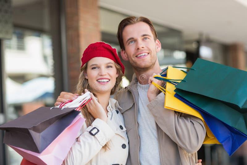Ett lyckligt par med shoppingpåsar royaltyfria bilder