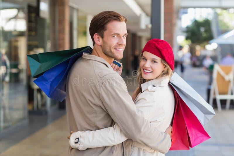 Ett lyckligt par med shoppingpåsar arkivfoto