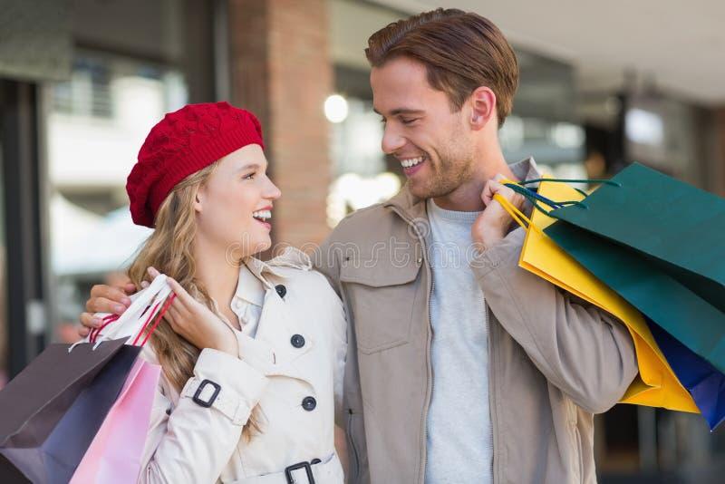 Ett lyckligt par med shoppingpåsar arkivfoton