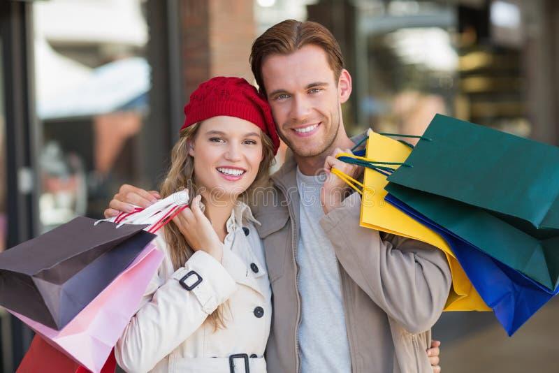 Ett lyckligt par med shoppingpåsar royaltyfria foton