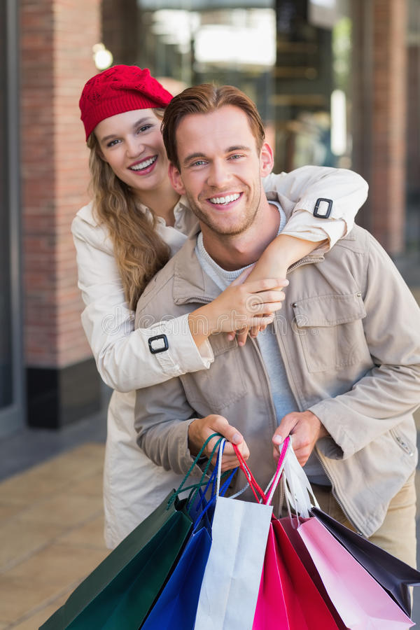 Ett lyckligt par med shoppingpåsar royaltyfri bild