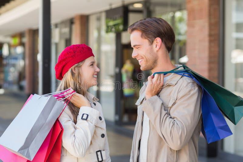 Ett lyckligt par med shoppingpåsar arkivbild