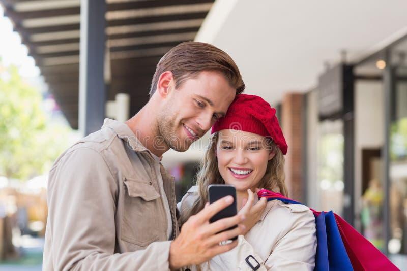 Ett lyckligt par som ser smartphonen arkivbilder
