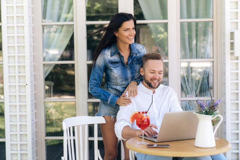 Ett lyckligt ungt par i ett kafé och att shoppa på internet och att koppla av och att dricka coctailar Internetbegrepp, teknologi royaltyfri foto