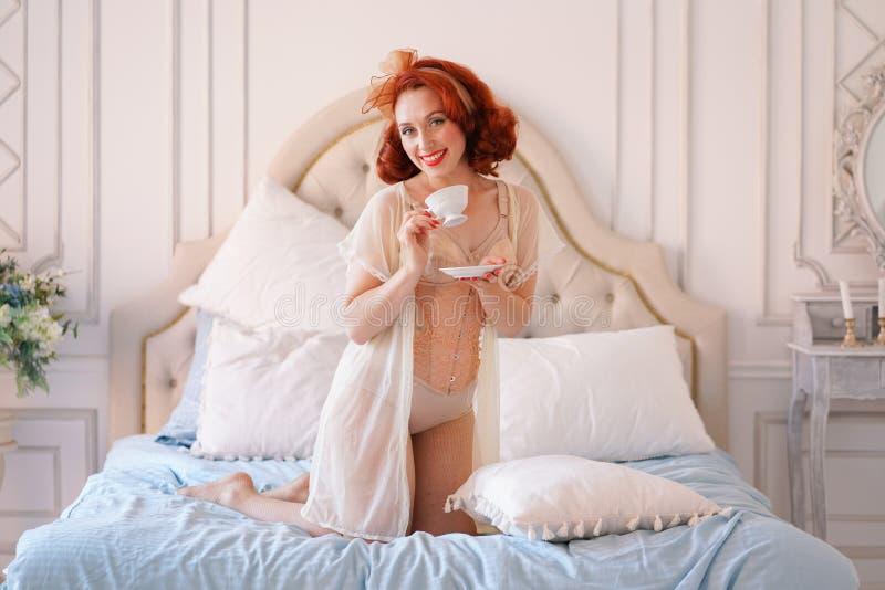 Ett lyxigt stift upp den iklädda damen en beige tappningdamunderkläder som poserar i hennes sovrum och, har en kopp av frukostte royaltyfria bilder