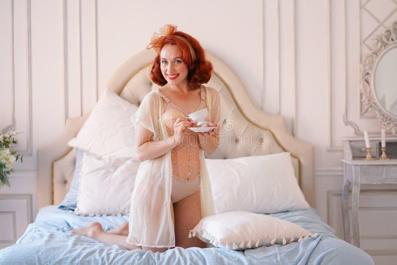 Ett lyxigt stift upp den iklädda damen en beige tappningdamunderkläder som poserar i hennes sovrum och, har en kopp av frukostte royaltyfri foto