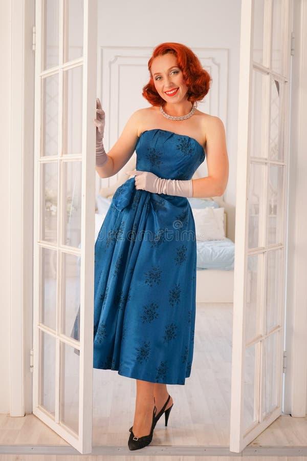 Ett lyxigt stift upp den iklädda damen en blå tappningklänning står i dörröppningen av hennes sovrum och inviterar dig att komma  royaltyfri bild