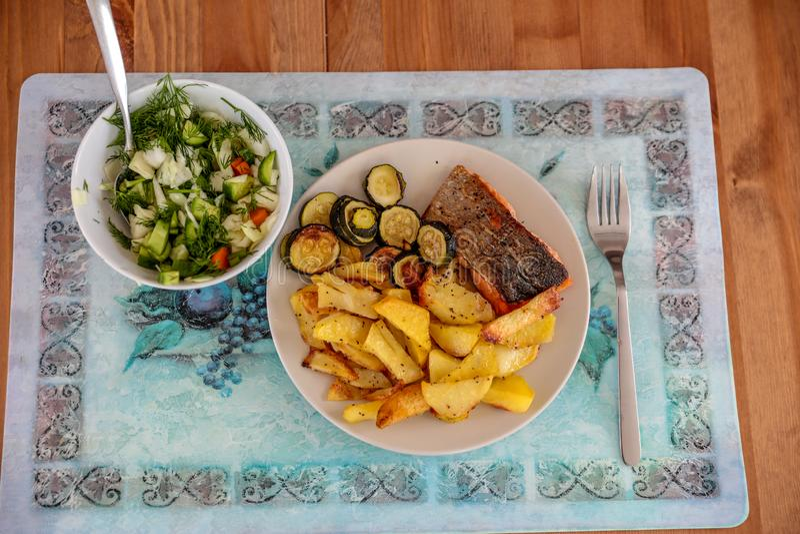 Ett mål som består av bakade potatisar med en stekt fisk och sallad royaltyfri fotografi