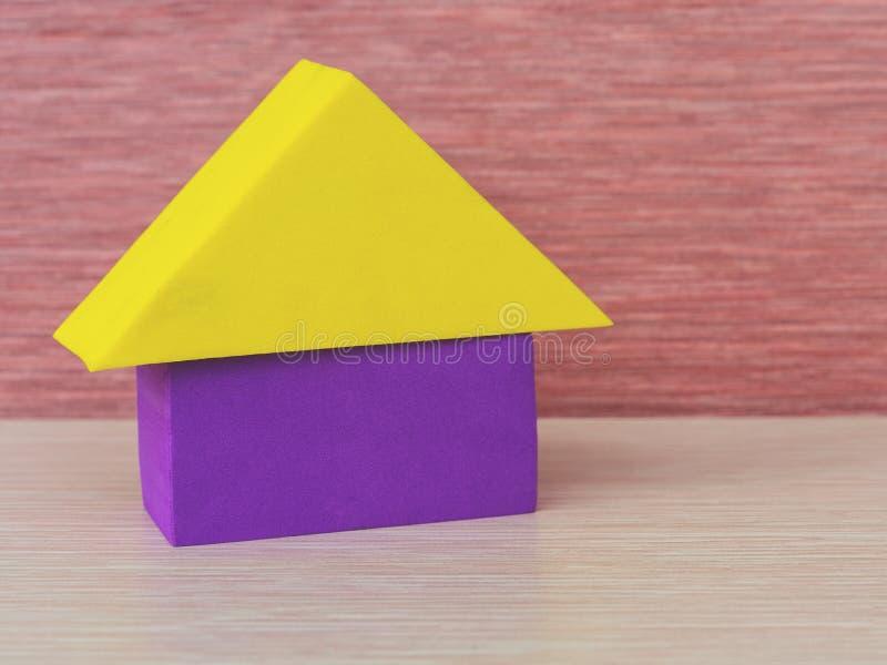 Ett mångfärgat gult purpurfärgat hus av byggnadskvarter triangel, rektangel, en bildande leksak för barn på en rosa bakgrund fotografering för bildbyråer
