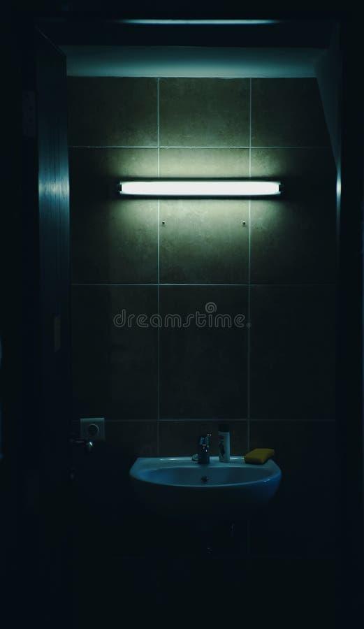 Ett mörkt badrum med ett dunkelt ljus arkivfoton