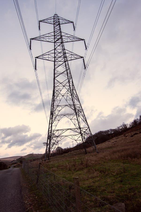 Ett mörkt stort överföringstorn, elektricitetspylon, står mot en gul solnedgång fotografering för bildbyråer