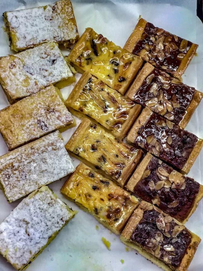 Ett magasin av sötsaker som är klara att ätas av något girigt efterrätter liksom bakelsebakelser är av många typer självfallet al royaltyfria foton