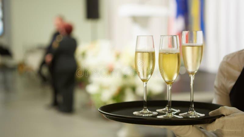 Ett magasin med tre exponeringsglas av champagne Uppassare som rymmer ett magasin med ett champagneexponeringsglas arkivbilder