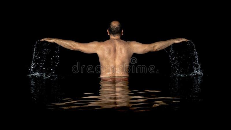 Ett mananseende inom vattnet och spridningarna hans armar arkivfoton