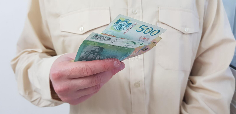 Ett mananseende som bär den ljusa kulöra officiella skjortan, rymmer i hans serbiska pappers- pengar för handen royaltyfri bild