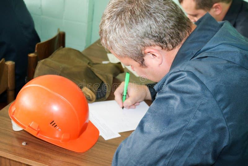 Ett manarbete som en tekniker med en hjälm för orange guling på tabellen studerar som skriver i en anteckningsbok på en industria arkivfoton