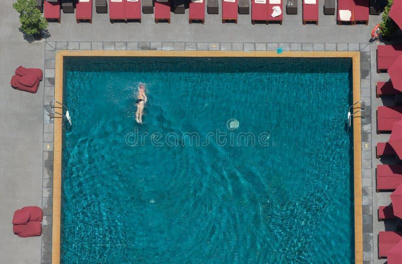 Ett manbad i pölen på hotellet med det röda strandparaplyet fotografering för bildbyråer