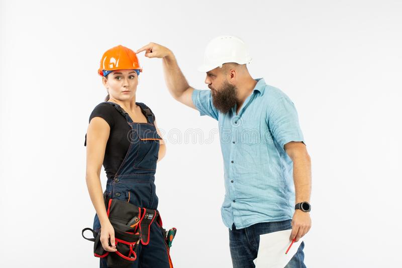 Ett manligt arkitekt- eller teknikermöte med en byggnadskvinnaleverantör på vit bakgrund royaltyfri bild