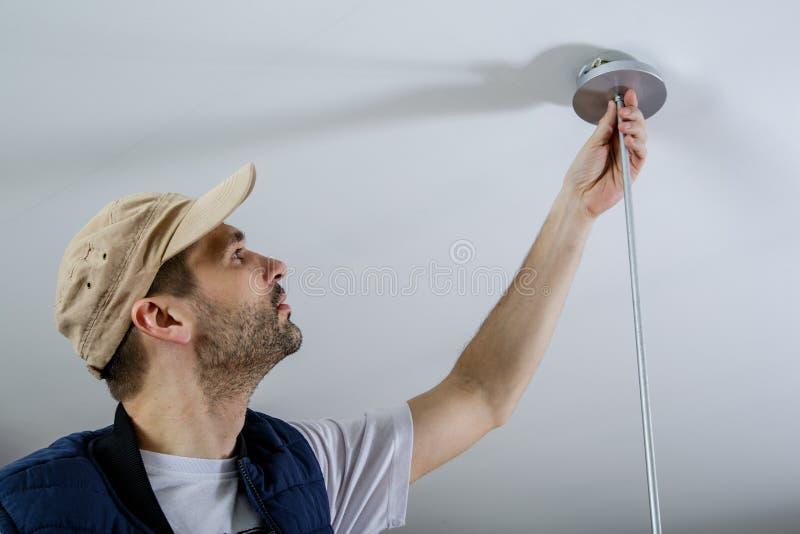 Ett manligt elektrikerfixandeljus på taket arkivbilder