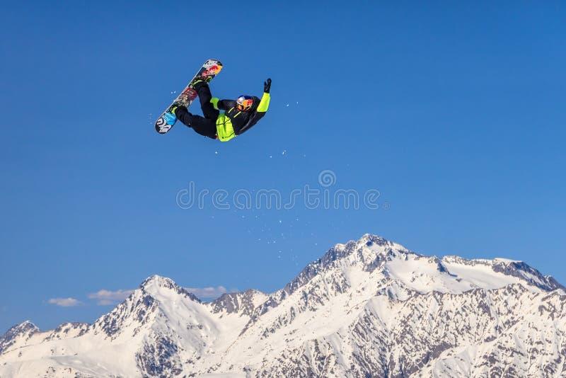 Ett manligt snowboardryttareflyg från ett skidahopp på snöig bergbakgrund arkivbilder