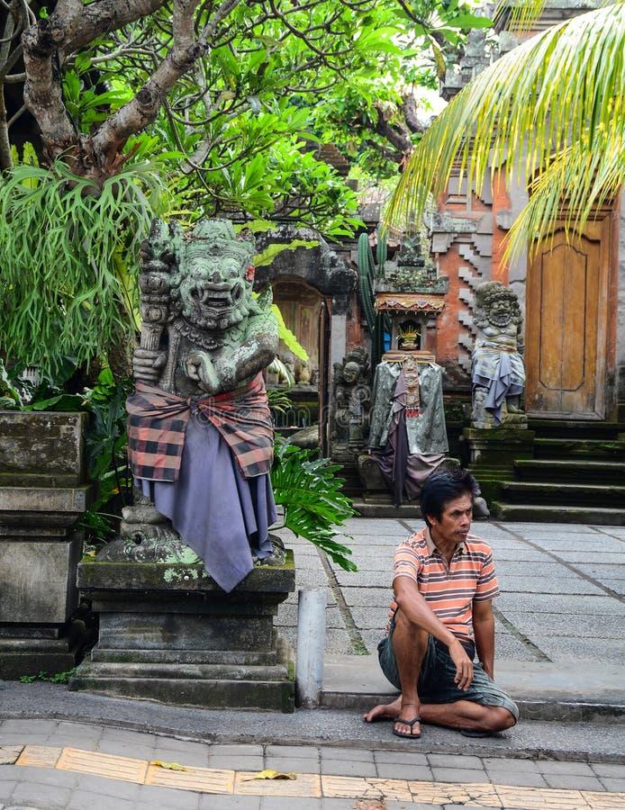 Ett mansammanträde på gatan i Bali, Indonesien royaltyfri bild