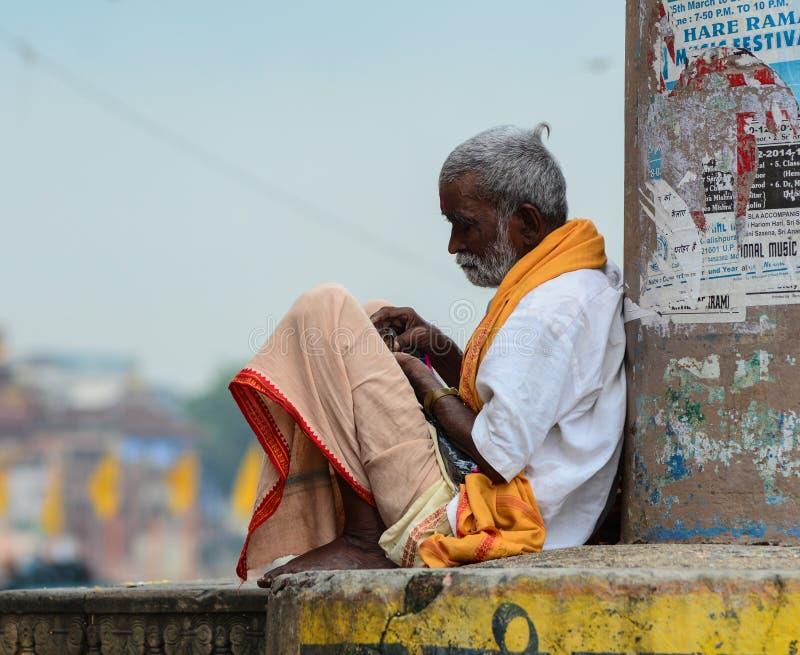 Ett mansammanträde på gatan i Varanasi, Indien royaltyfria foton