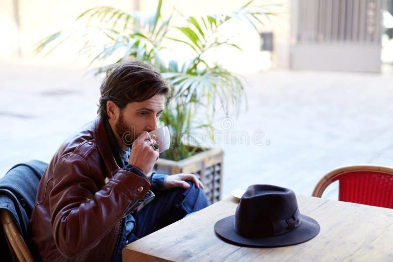 Ett mansammanträde på terrassen som dricker kaffe och väntar på hans vän royaltyfri bild