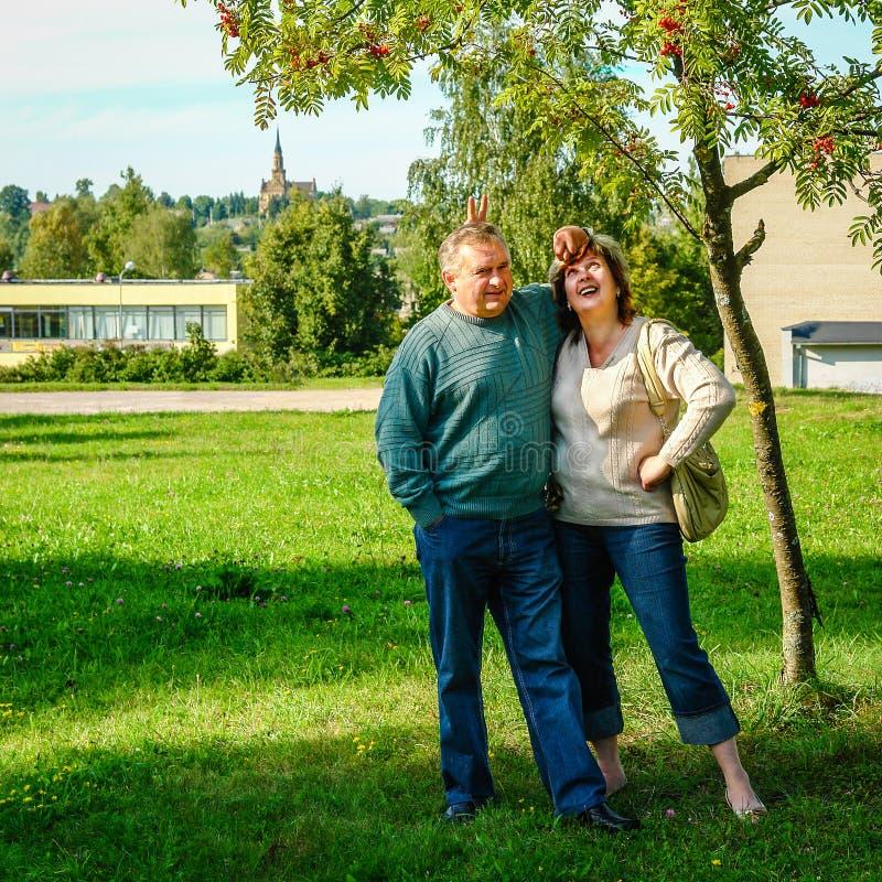 Ett medelålderst par står under ett träd arkivbild