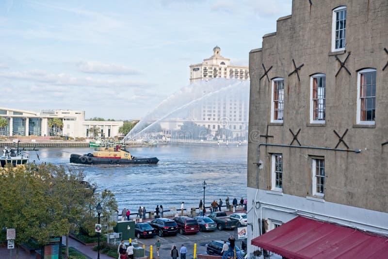 Ett medel för bogserbåtfartyghjälp reser bak en handels- skyttel som besprutar vatten royaltyfri bild