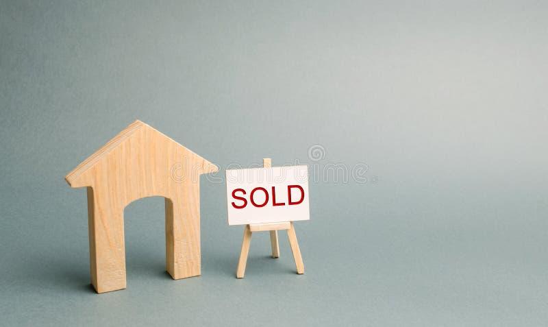 Ett miniatyrtr?hus och en affisch med inskriften s?lde Begreppet av att s?lja egenskapen och fastigheten S?ld l?genhet royaltyfri fotografi