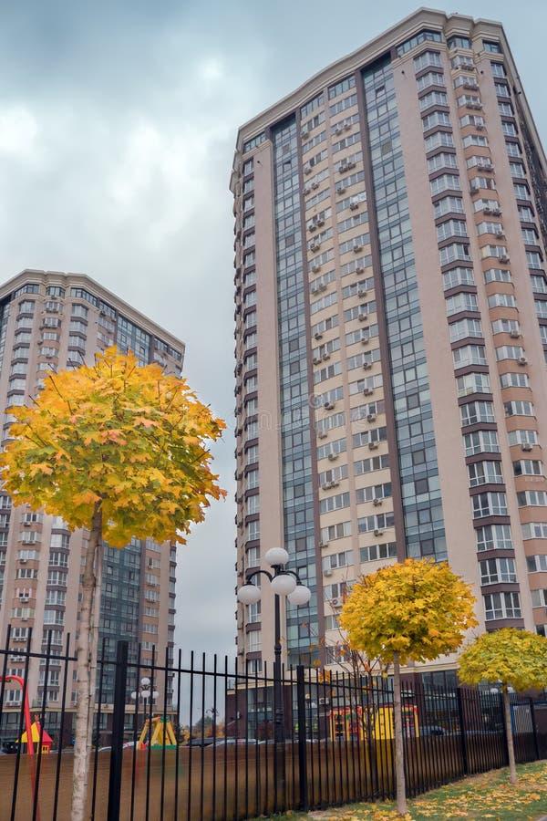 Ett modernt hus med ett propert angränsande territorium och läckra gula träd för en lönn nedanför veiw royaltyfri foto